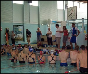 Russ Barber talks to the swimmers while Braxton Timm looks on